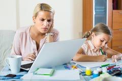 Усиленная женщина при ребенок работая от дома Стоковое фото RF