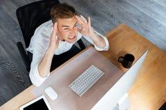 Усиленный бизнесмен работая с компьютером и имея головную боль в офисе Стоковая Фотография