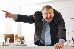 Усиленный вне работник крича на его товарищеском работнике офиса Стоковые Изображения