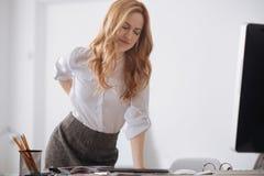 Усиленный молодой менеджер касаясь ей болея назад в офисе Стоковые Изображения RF