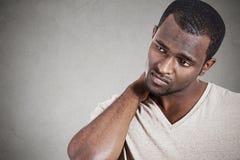 Усиленный, несчастный молодой красивый человек с болью шеи стоковая фотография