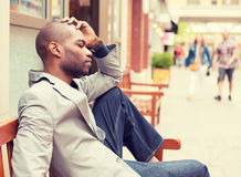 Усиленный унылый молодой вскользь бизнесмен сидя вне корпоративного офиса Стоковая Фотография