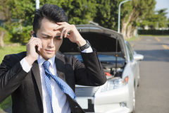 Усильте бизнесмена вызывая для помощи с концепцией сломанной автомобилем Стоковые Изображения RF