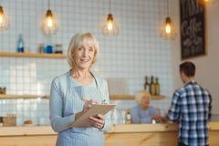 Услаженная жизнерадостная женщина работая в кофейне Стоковые Изображения