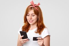 Услаженная молодая foxy женщина при haedband, одетое в вскользь белой футболке, держит современный сотовый телефон и кредитная ка стоковое изображение rf