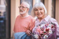 Услаженная старуха идя с человеком на улице стоковые фотографии rf