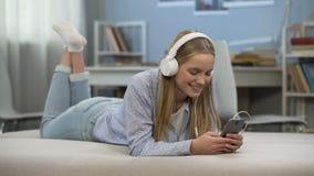 Услаженные наушники девочка-подростка нося, слушая к музыке, время релаксации сток-видео
