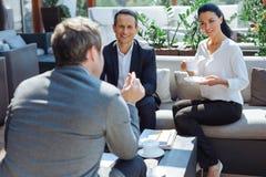 Услаженные радостные коллеги говоря друг к другу Стоковая Фотография RF