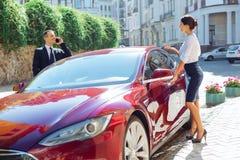 Услаженные славные деловые партнеры получая в автомобиль Стоковые Изображения