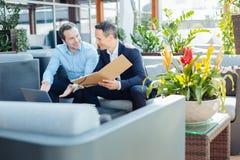 Услаженные умные бизнесмены говоря друг к другу Стоковая Фотография