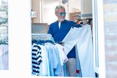 Услаженный пожилой клиент смотря выбранные брюки стоковое изображение rf