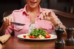 Услаженный язык выставки женщины и идти съесть салат с arugula Стоковые Фото