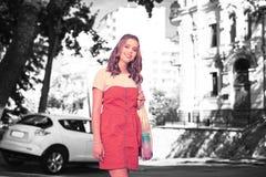 Усмехаться апеллирующ молодая женщина с прозрачным положением хозяйственной сумки около автомобиля стоковые фотографии rf