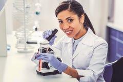 Усмехаться апеллирующ химик смотря в микроскоп стоковые изображения rf