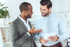 усмехаться Афро-американские и кавказские бизнесмены говоря на офисе Стоковые Изображения RF