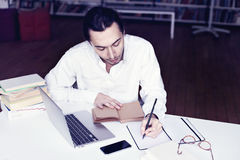 Усмехаться бизнесмена или студента университета, работая на компьтер-книжке читая книгу в библиотеке Стоковые Фото
