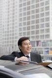 Усмехаться бизнесмена, работая outdoors на автомобиле Стоковые Изображения RF