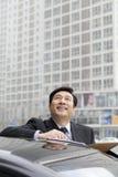 Усмехаться бизнесмена, работая outdoors на автомобиле Стоковое фото RF