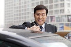 Усмехаться бизнесмена, работая outdoors на автомобиле Стоковое Изображение RF