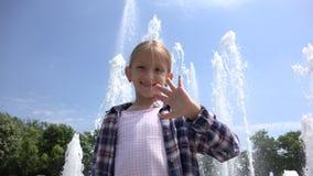 Усмехаться в камере, ослаблять ребенка развевая до свидания девушки на открытом воздухе в летнем дне 4K видеоматериал