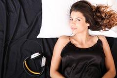 Усмехаться в кровати с шлемофонами Стоковые Фотографии RF