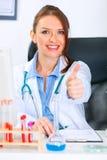 усмехаться доктора медицинский показывая thumbs вверх по женщине Стоковое Изображение