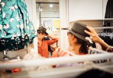 Усмехаться женский пробует дальше новый взгляд шляпы на отражении зеркала Стоковые Фотографии RF