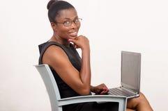 Усмехаться женщины сидя пока работающ на концепции мобильного офиса стоковые изображения