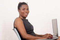 Усмехаться женщины сидя пока работающ на концепции мобильного офиса стоковое фото