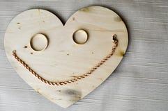 Усмехаться, жизнерадостная кружка сделанная от деревянного сердца к дню ` s валентинки, wedding кольца золота и женская цепь золо Стоковая Фотография