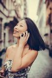 Усмехаться используя мобильный телефон Стоковая Фотография