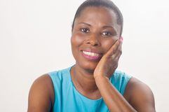 Усмехаться и уверенно женщина сидя с ее рукой на ее щеке стоковая фотография