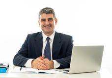 Усмехаться и уверенный серый с волосами исполнительный бизнесмен с деятельностью ноутбука и занимающся серфингом в Интернете в де стоковое фото