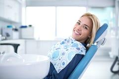 Усмехаться и удовлетворенный пациент в зубоврачебном офисе стоковые изображения