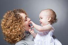 усмехаться мати удерживания младенца милый счастливый Стоковое Изображение