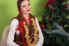 Усмехаться мечтающ сельская женщина с бейгл в шали в Новогодней ночи Стоковые Изображения RF