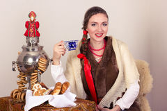 Усмехаться мечтающ сельская женщина с бейгл и чашкой тройника в шали в Новогодней ночи Стоковые Фото