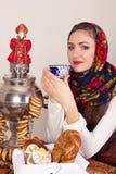 Усмехаться мечтающ сельская женщина с бейгл и чашкой тройника в шали в Новогодней ночи Стоковые Изображения RF