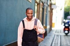 Усмехаться молодого чернокожего человека идя вниз по улице стоковые фото