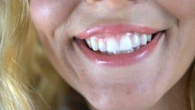 Усмехаться молодой женщины задушевно, показывая ее белые здоровые зубы, зубоврачебные обслуживания акции видеоматериалы