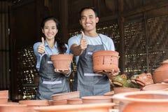 Усмехаться мужской и женский гончар держа их продукт в гончарне стоковое изображение