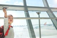 Усмехаться немного азиат 2 старого лет ребенка мальчика малыша имея потеху играя с игрушкой самолета пока ждущ его полет на авиап стоковые фото