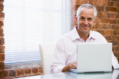 усмехаться офиса компьтер-книжки бизнесмена сидя Стоковые Фотографии RF