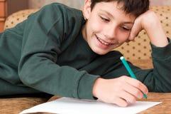 усмехаться письма мальчика пишет стоковые фото