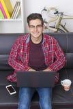Усмехаться предназначенный для подростков на кресле с компьтер-книжкой стоковые фото