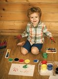 Усмехаться ребенка счастливый с покрашенными руками, красками гуаши и чертежами Стоковая Фотография RF