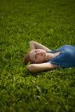 усмехаться травы девушки лежа стоковые изображения