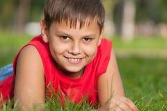 усмехаться травы мальчика красный стоковые фото