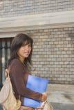 усмехаться девушки коллежа Стоковая Фотография