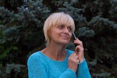 Усмехаться ellderly женщина имеет переговор телефоном стоковое изображение